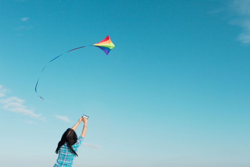 173807238 - L - Woman flying kite outdoors